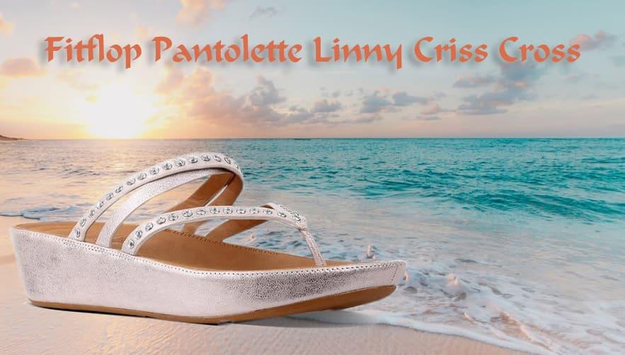 Fitflop Pantolette Linny Criss Cross vor Sonnenuntergang am Strand.