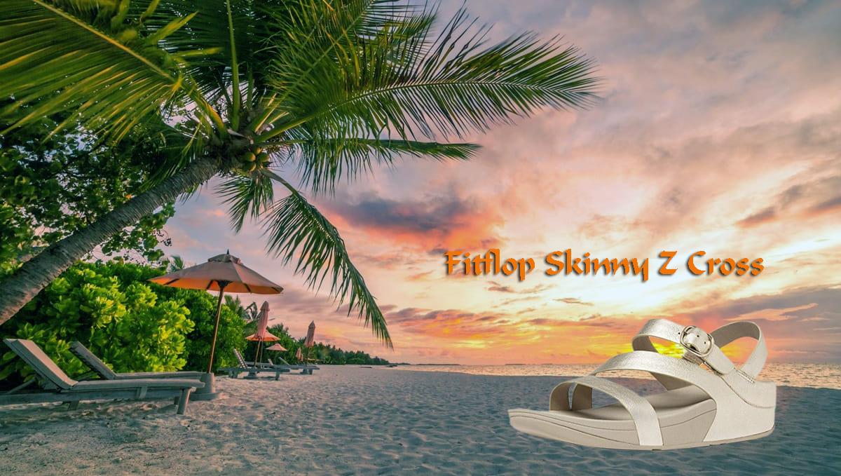 FitFlop Sandale Skinny-Z-Cross vor Sonnenuntergang am Strand.